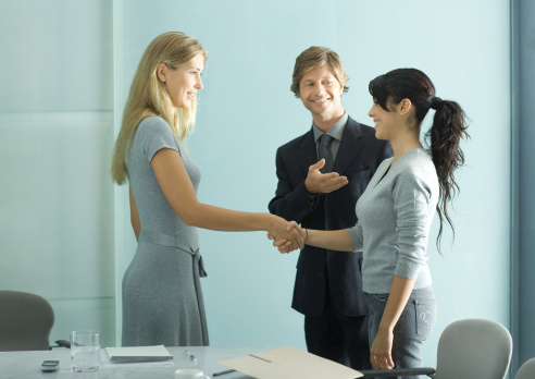 Businessman introducing teenage girl to young professional woman